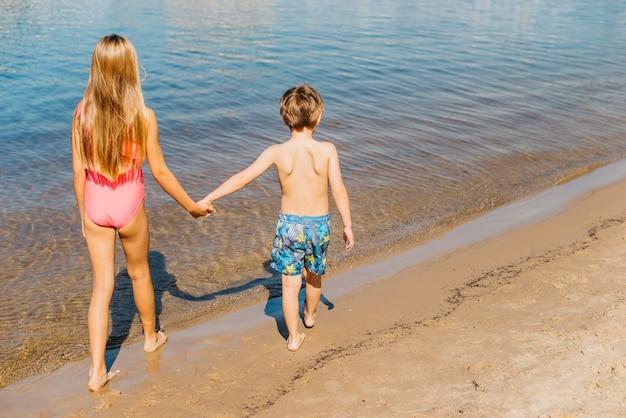 Bambini che camminano lungo la costa