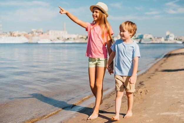 Bambini che camminano lungo la spiaggia