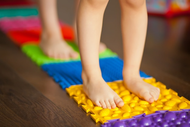 Bambini che camminano su un tappetino da massaggio ortopedico. trattamento e prevenzione dei piedi piatti nei bambini.