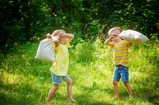 Bambini che combattono insieme ai cuscini in un giardino estivo soleggiato