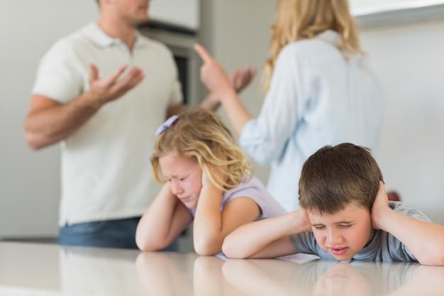 Bambini che coprono le orecchie mentre i genitori litigano