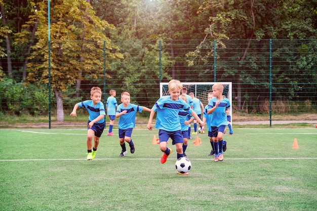 Bambini che corrono e calciano palloni da calcio durante la sessione di allenamento di calcio per bambini