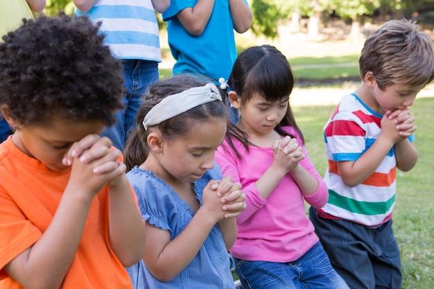 Bambini che dicono le loro preghiere nel parco