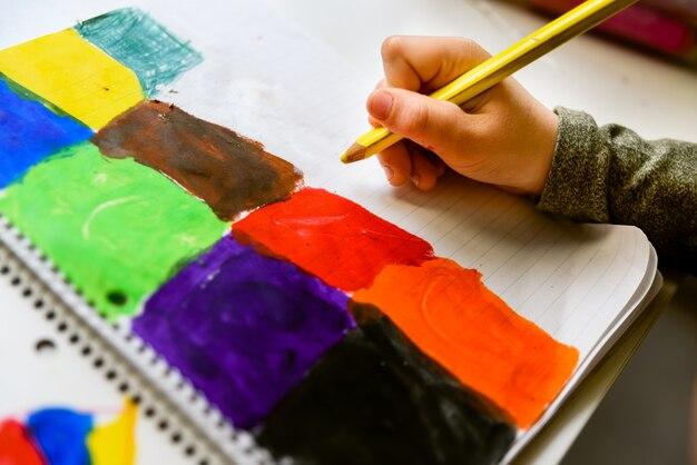 Bambini che dipingono quadri con colori vivaci mentre sviluppano la sua creatività.