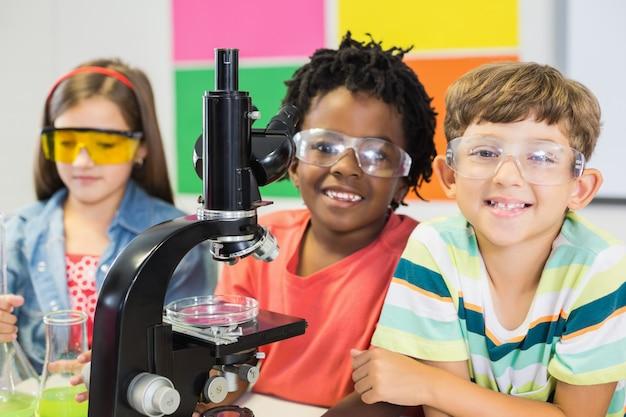 Bambini che fanno esperimento sul microscopio in laboratorio