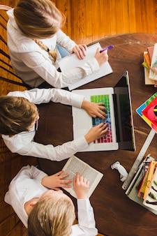 Bambini che fanno i compiti con il computer portatile
