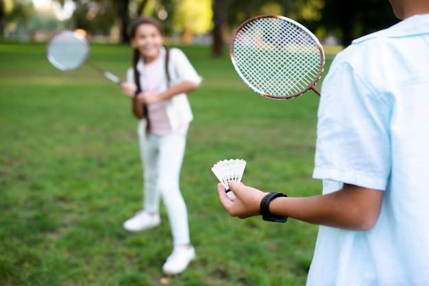Bambini che giocano a badminton in bella giornata estiva
