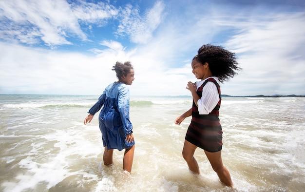 Bambini che giocano a correre sulla sabbia in spiaggia