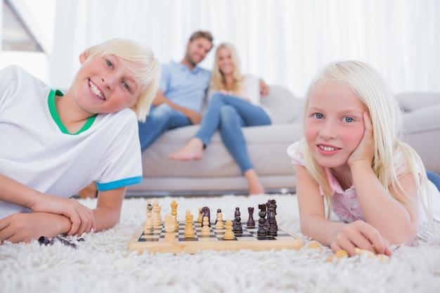 Bambini che giocano a scacchi davanti ai loro genitori
