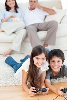 Bambini che giocano ai videogiochi mentre i genitori parlano