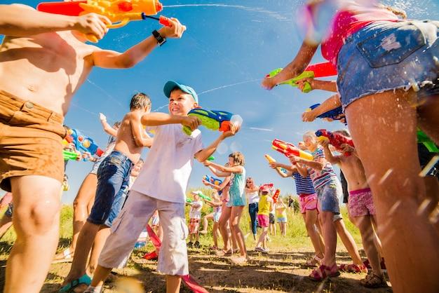 Bambini che giocano all'aperto con cannoni ad acqua in una bella giornata di sole