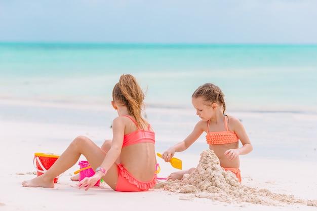 Bambini che giocano con i giocattoli da spiaggia sulla spiaggia bianca