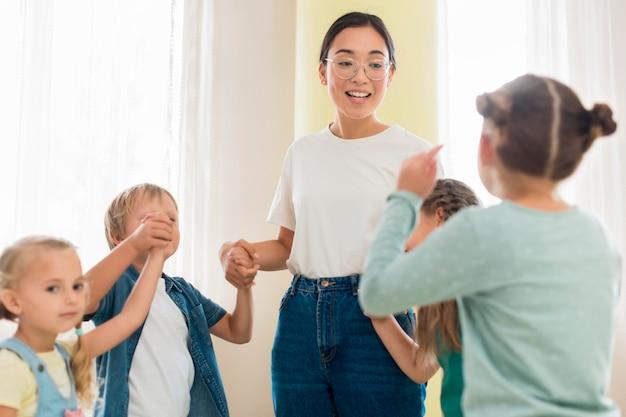 Bambini che giocano con la loro maestra d'asilo