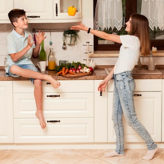 Bambini che giocano con la verdura in cucina