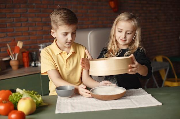 Bambini che giocano con una farina in una cucina