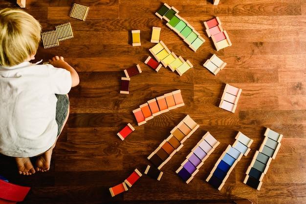 Bambini che giocano e imparano con tavolette di colore montessori