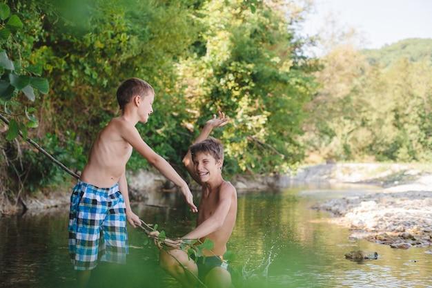 Bambini che giocano e spruzzi nel fiume