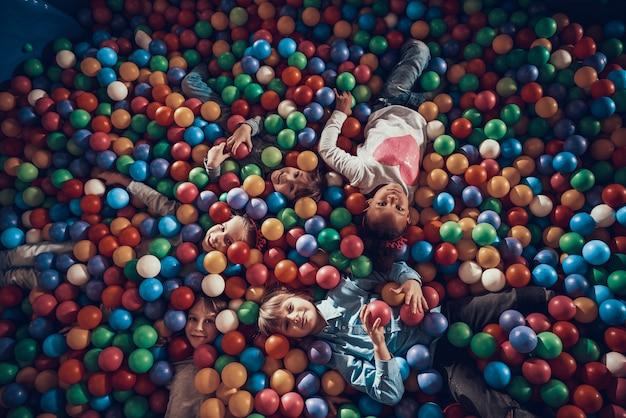 Bambini che hanno divertimento insieme sul moderno parco giochi al coperto.