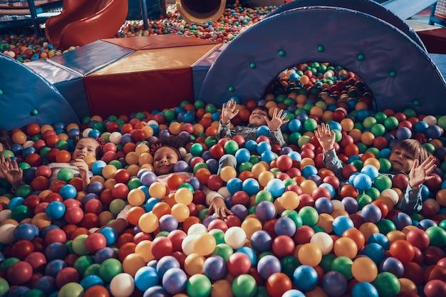Bambini che hanno divertimento insieme sul moderno parco giochi al coperto