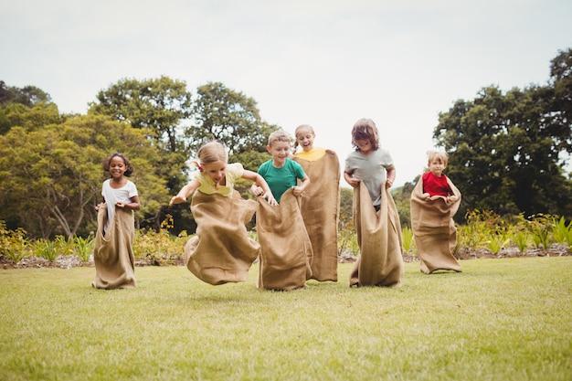 Bambini che hanno una corsa al sacco