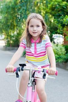 Bambini che imparano a guidare una bicicletta su un vialetto esterno.