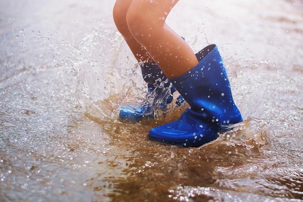Bambini che indossano stivali da pioggia e saltano nella pozzanghera in una giornata piovosa