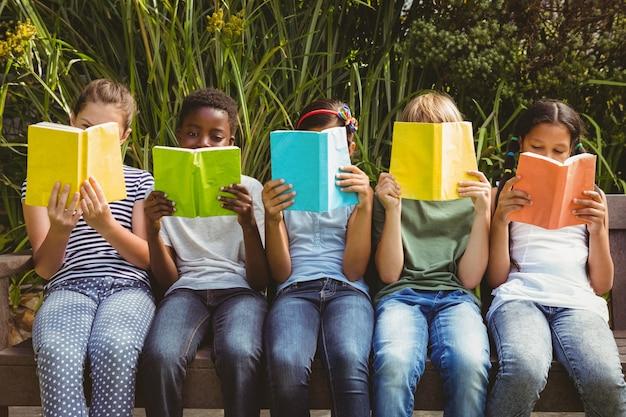 Bambini che leggono libri al parco