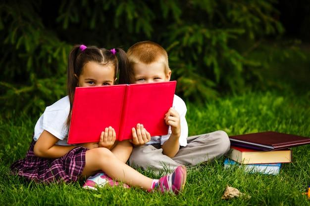 Bambini che leggono un libro nel giardino estivo