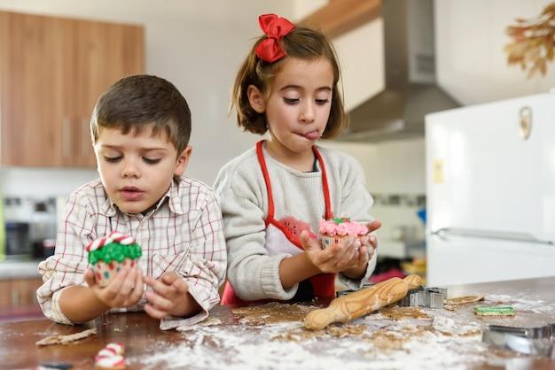 Bambini che mangiano i biscotti di natale e torte della tazza in cucina