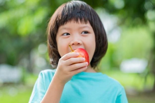Bambini che mangiano una mela nel verde della natura