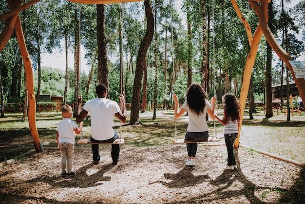 Bambini che oscillano i genitori sulla giornata di sole estivo di altalene