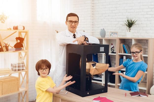 Bambini che posano sulla macchina fotografica con l'insegnante e la stampante 3d.