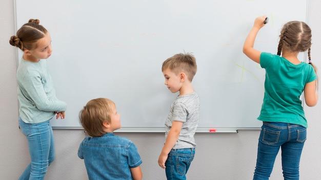 Bambini che scrivono su una lavagna bianca