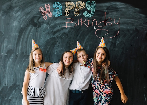 Bambini che si abbracciano vicino a scrivere buon compleanno