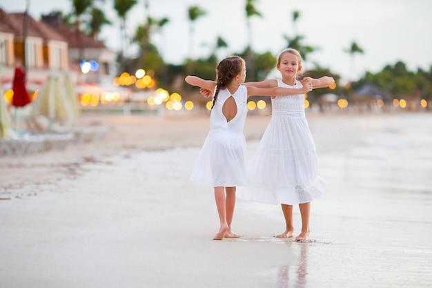 Bambini che si divertono a ballare in spiaggia tropicale e divertirsi