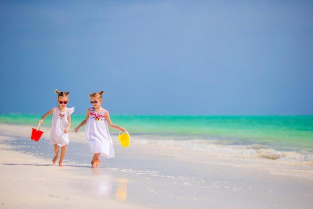 Bambini che si divertono in spiaggia tropicale giocando insieme in acque poco profonde