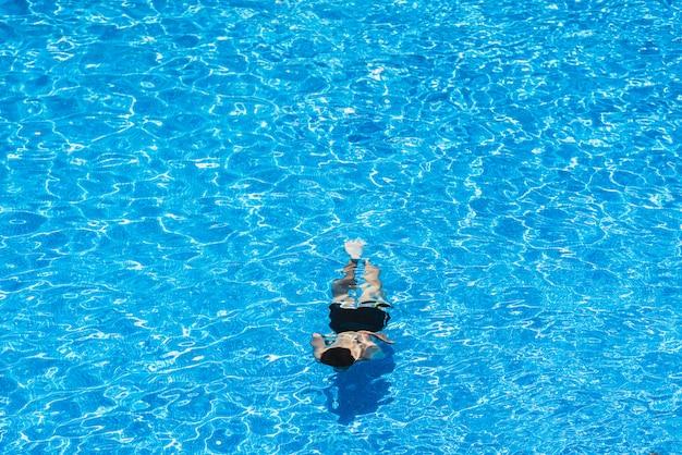 Bambini che si tuffano in una piscina in estate