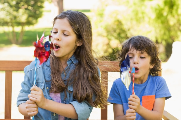 Bambini che soffia girandole su panchina