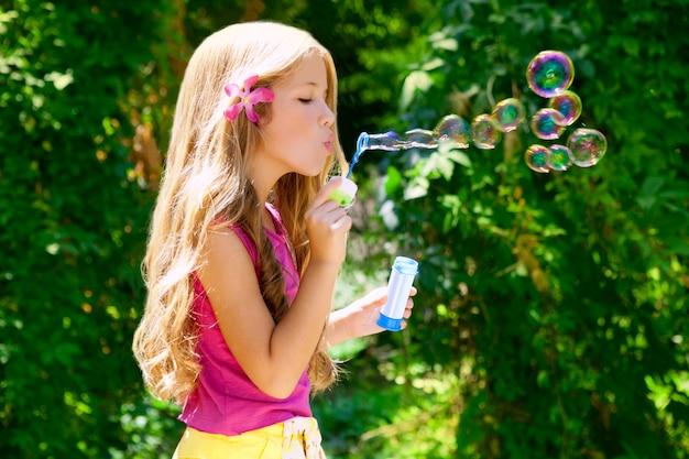 Bambini che soffiano bolle di sapone nella foresta all'aperto