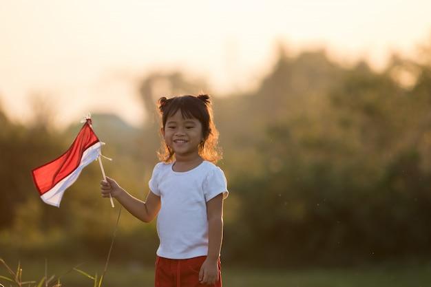 Bambini che sollevano bandiera indonesiana