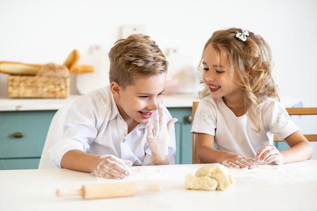 Bambini che sorridono mentre si prepara l'impasto per dolci a casa