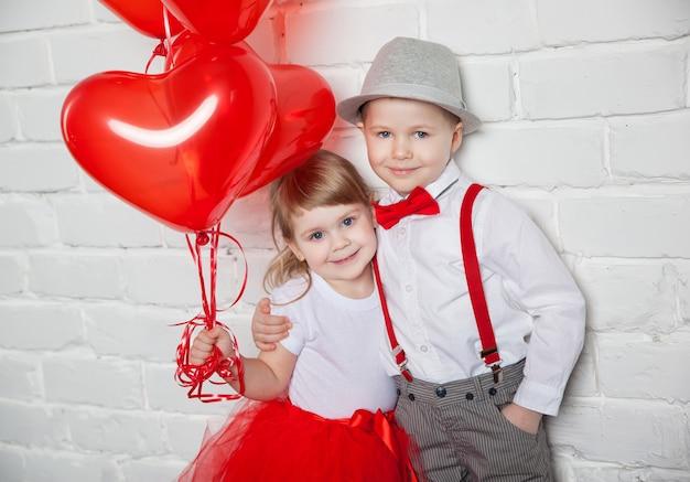 Bambini che tengono e raccogliendo palloncini cuore. san valentino e concetto di amore, su fondo bianco