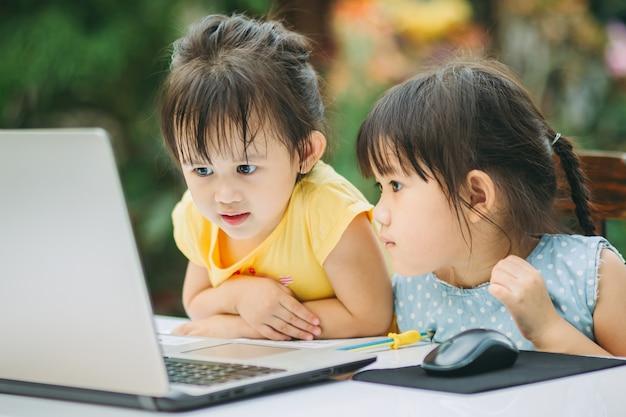Bambini che utilizzano computer portatile per lo studio a casa.