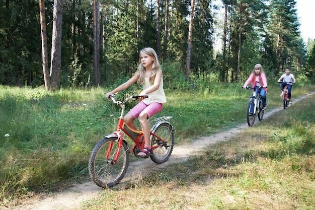 Bambini che vanno in bicicletta nei boschi