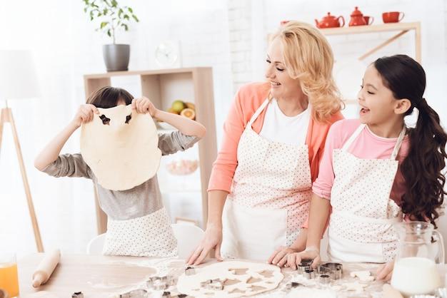Bambini con la nonna divertendosi sul concetto della cucina