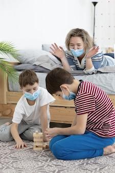 Bambini con maschere mediche che giocano a jenga a casa con la madre