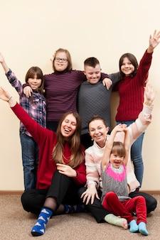Bambini con sindrome di down e donna in posa felicemente