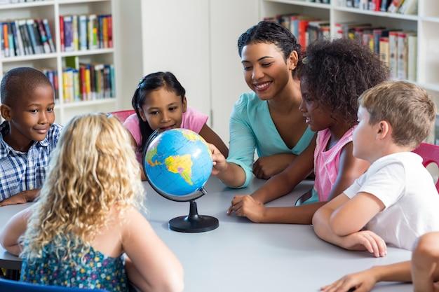 Bambini d'istruzione dell'insegnante femminile che usando globo