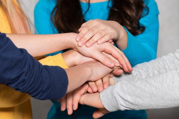 Bambini del primo piano che formano la pila delle mani