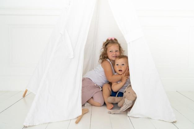 Bambini della foto a figura intera che abbracciano sotto la tenda